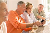 Senior couples drinking wine and looking at cell phone Stock Photo - Premium Royalty-Freenull, Code: 6113-07242055