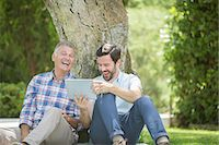 Father and son using digital tablet outdoors Stock Photo - Premium Royalty-Freenull, Code: 6113-07242061