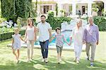 Multi-generation family holding hands and walking in backyard
