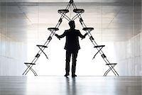 Businessman arranging office chair installation art Stock Photo - Premium Royalty-Freenull, Code: 6113-07242159