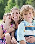 Mother and children smiling outdoors