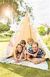 Family relaxing in teepee in backyard