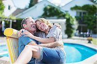 Couple relaxing in lounge chair at poolside Stock Photo - Premium Royalty-Freenull, Code: 6113-07242304