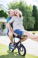Couple riding small bicycle in grass Stock Photo - Premium Royalty-Freenull, Code: 6113-07242328
