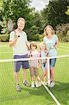 Family smiling together on grass tennis court