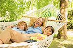 Mother and children relaxing in hammock