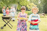 Brother and sister holding grilled corn near barbecue in backyard Stock Photo - Premium Royalty-Freenull, Code: 6113-07242362