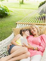 Grandmother and granddaughter with digital tablet in hammock Stock Photo - Premium Royalty-Freenull, Code: 6113-07242363