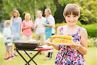 Smiling girl holding grilled corn in backyard Stock Photo - Premium Royalty-Freenull, Code: 6113-07242374