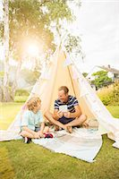 Father and son using digital tablet in teepee in backyard Stock Photo - Premium Royalty-Freenull, Code: 6113-07242392