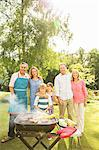Multi-generation family standing at barbecue in backyard