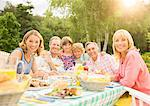 Multi-generation family enjoying lunch at table in backyard