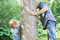 Father and son peeking around tree Stock Photo - Premium Royalty-Freenull, Code: 6113-07242409