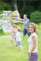 Family playing with bubbles in backyard Stock Photo - Premium Royalty-Freenull, Code: 6113-07242445