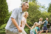 Multi-generation family holding hands and running Stock Photo - Premium Royalty-Freenull, Code: 6113-07242451