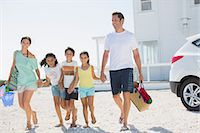 Family holding hands and walking with beach gear in sunny driveway Stock Photo - Premium Royalty-Freenull, Code: 6113-07242554