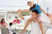 Father carrying daughter on shoulders on sunny patio Stock Photo - Premium Royalty-Freenull, Code: 6113-07242559