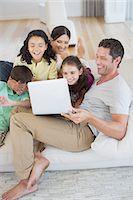 preteen family - Family using laptop on sofa in living room Stock Photo - Premium Royalty-Freenull, Code: 6113-07242613