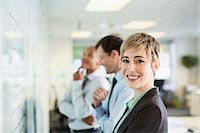 strategy - Businesswoman smiling at whiteboard in office Stock Photo - Premium Royalty-Freenull, Code: 6113-07242730