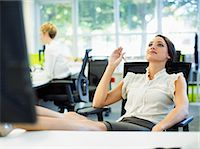 Businesswoman relaxing with feet up on desk in office Stock Photo - Premium Royalty-Freenull, Code: 6113-07242733
