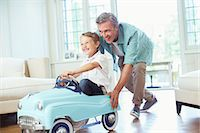 Father pushing son in toy car Stock Photo - Premium Royalty-Freenull, Code: 6113-07242785