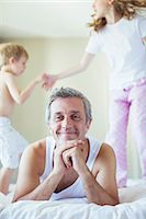 Children jumping on bed around father Stock Photo - Premium Royalty-Freenull, Code: 6113-07242799
