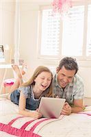 Father and daughter using digital tablet on bed Stock Photo - Premium Royalty-Freenull, Code: 6113-07242831