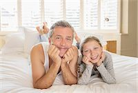 Father and daughter laying on bed Stock Photo - Premium Royalty-Freenull, Code: 6113-07242847