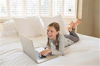 Girl using laptop on bed Stock Photo - Premium Royalty-Freenull, Code: 6113-07242852