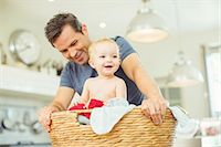Father carrying baby in laundry basket Stock Photo - Premium Royalty-Freenull, Code: 6113-07242888