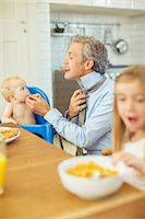 Father and children eating breakfast in kitchen Stock Photo - Premium Royalty-Freenull, Code: 6113-07242893