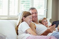 Father and children using digital tablet on bed Stock Photo - Premium Royalty-Freenull, Code: 6113-07242913