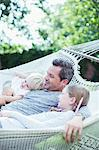 Father and children relaxing in hammock