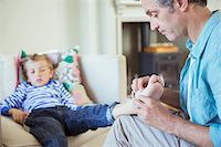 Father bandaging son's foot Stock Photo - Premium Royalty-Freenull, Code: 6113-07242946