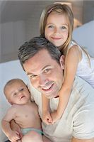Father and children relaxing on bed Stock Photo - Premium Royalty-Freenull, Code: 6113-07242954