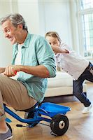 Boy pushing father on tricycle indoors Stock Photo - Premium Royalty-Freenull, Code: 6113-07242962