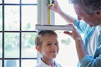 Father measuring son's height on wall Stock Photo - Premium Royalty-Freenull, Code: 6113-07242973