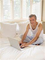 Man using laptop on bed Stock Photo - Premium Royalty-Freenull, Code: 6113-07243013