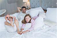 Father and children relaxing on bed Stock Photo - Premium Royalty-Freenull, Code: 6113-07243014