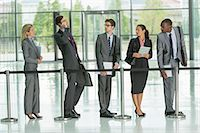 Businessman talking on cell phone in line Stock Photo - Premium Royalty-Freenull, Code: 6113-07243117