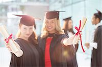 Smiling graduates holding diplomas Stock Photo - Premium Royalty-Freenull, Code: 6113-07243319