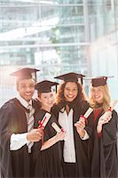 Smiling graduates holding diplomas Stock Photo - Premium Royalty-Freenull, Code: 6113-07243346