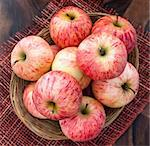 Fresh red apples in basket on the wooden table, top view