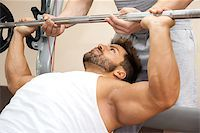 A handsome young muscular sports man doing bench press with a little help Stock Photo - Royalty-Freenull, Code: 400-07255272