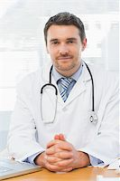 Portrait of a smiling male doctor with laptop sitting at desk in medical office Stock Photo - Royalty-Freenull, Code: 400-07274834