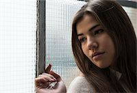 sad girls - Close-up portrait of young woman standing in front of window, day dreaming and looking into the distance, Germany Stock Photo - Premium Royalty-Freenull, Code: 600-07278935