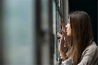 Portrait of young woman standing and looking out of window day dreaming, Germany Stock Photo - Premium Royalty-Freenull, Code: 600-07278938