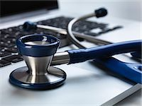 Stethoscope sitting on laptop illustrating online healthcare and doctor's desk Stock Photo - Premium Royalty-Freenull, Code: 649-07279535