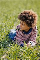 Portrait of boy lying on grass in sunlight Stock Photo - Premium Royalty-Freenull, Code: 649-07280024