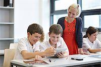 Schoolchildren working in class with teacher Stock Photo - Premium Royalty-Freenull, Code: 649-07280086